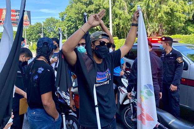 Jatupat Boonpathararaksa, arms raised, arrives at Thung Song Hong police station on Monday to answer a charge of defacing the station with red paint last Tuesday.  (Photo: Jatupat Boonpathararaksa Facebook account)