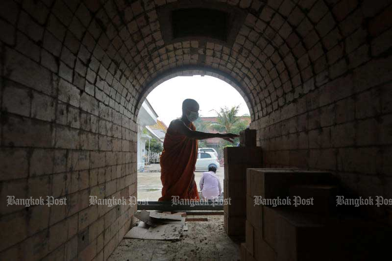 A monk works on a new furnace in the crematorium at Wat Chinwararam in Pathum Thani's Muang district on July 26, 2021. The temple is building six new furnaces to accommodate the increasing demand for cremations amid the pandemic. (Photo: Chanat Katanyu)