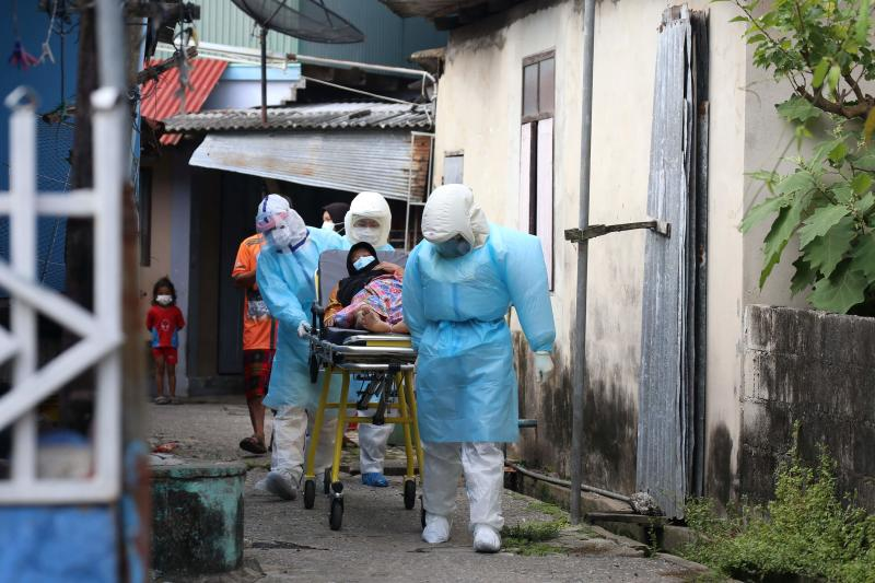 FILE PHOTO: Workers clad in PPE gear wheel a patient with Covid-19 symptoms to be brought to hospital from a village in Pattani on July 19, 2021, as Thailand seeks to contain a surge in coronavirus cases. (AFP)