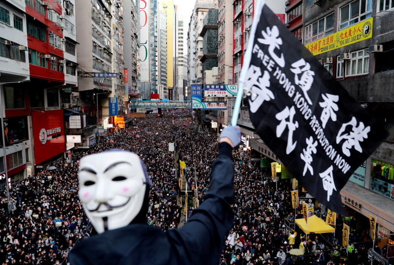 A protester wearing a Guy Fawkes mask waves a flag during a Human Rights Day march, organised by the Civil Human Right Front, in Hong Kong on Dec 8, 2019. (Reuters photo)