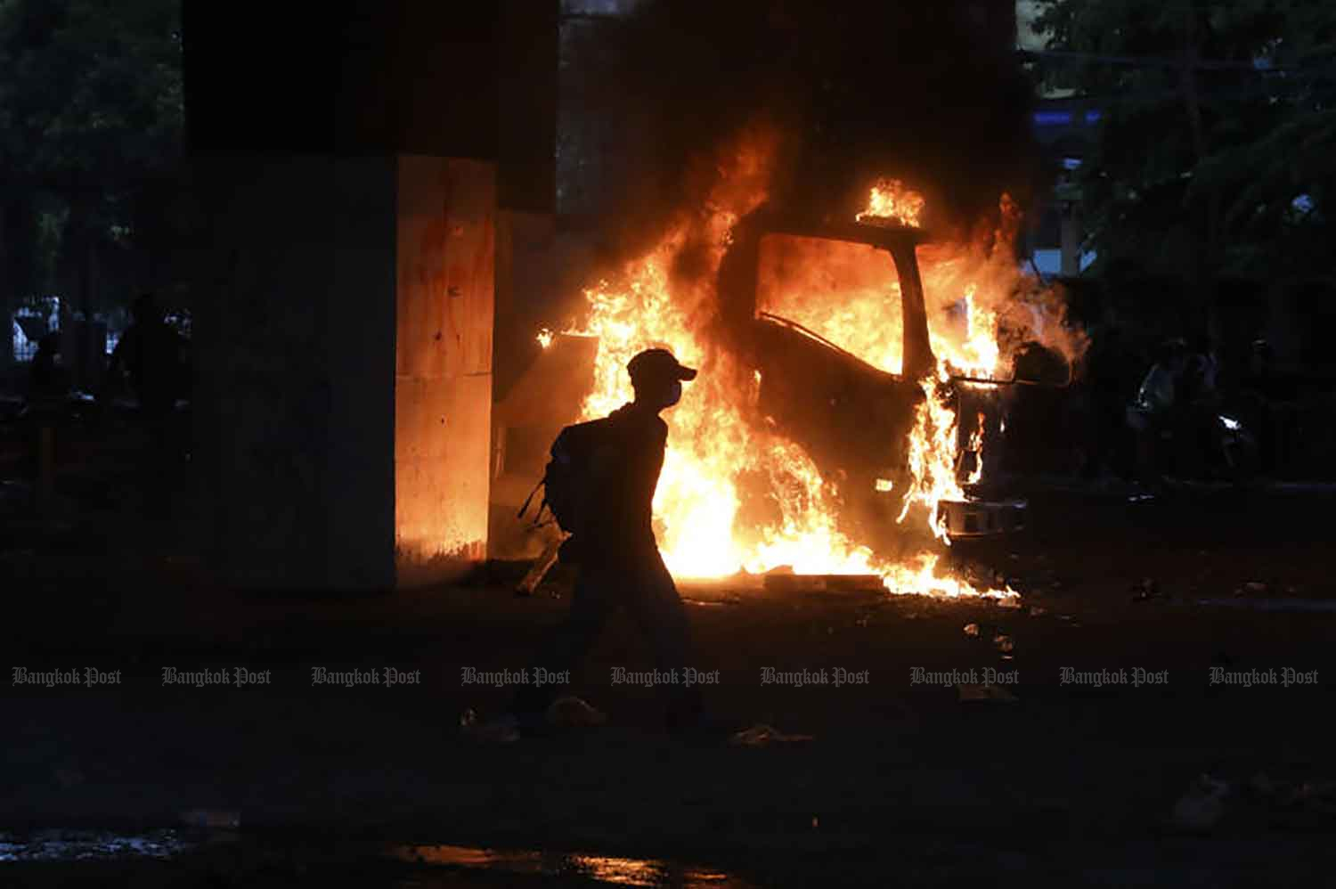 A protester walks past a burning police truck near the Victory Monument in Bangkok on Wednesday evening. (Photo: Arnun Chonmahatrakool)