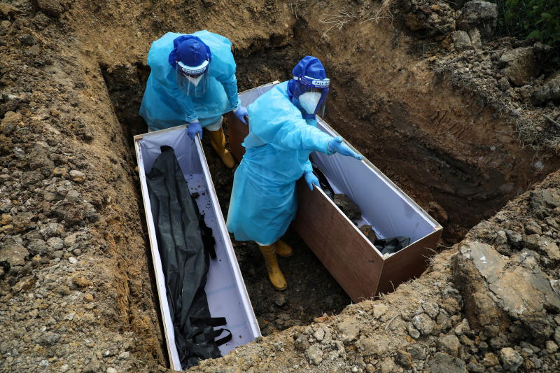 FILE PHOTO: Cemetery workers wearing protective suits bury victims of the coronavirus disease at a cemetery in Klang, Malaysia July 24, 2021. (Reuters)
