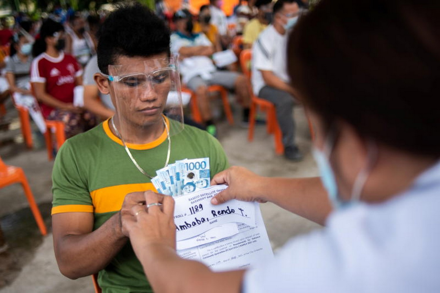 A man receives cash assistance from the Philipines government following the imposition of a two-week lockdown to prevent the spread of the coronavirus Delta variant, at an elementary school in Manila on Aug 11. (Photo: Reuters)