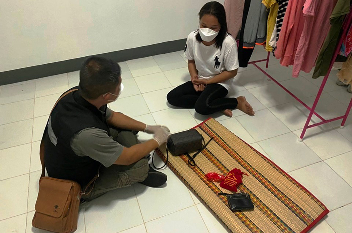 A police officer in Nakhon Phanom interviews a woman arrested in connection with eight break-ins in Muang district. (Photo: Pattanapong Sripiachai)