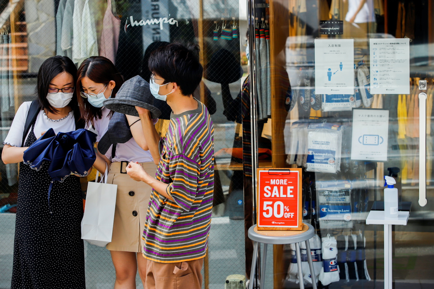 People wearing masks stand outside a shop with infection prevention instructions in its window in the Harajuku shopping area of Tokyo. (Reuters Photo)