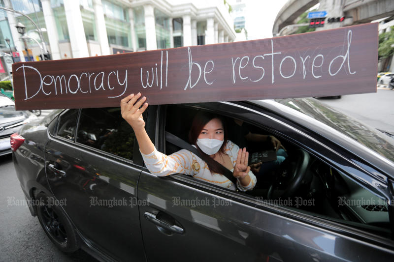 A driver shows a banner during a rally demanding Prime Minister Prayut Chan-o-cha to resign on Wednesday. (Photo: Chanat Katanyu)