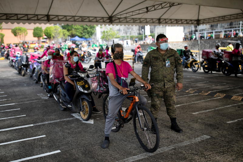 Service delivery riders queue to get vaccinated with Sinovac Covid-19 vaccine in a shopping mall parking lot turned into a drive-thru vaccination site in Quezon City, Metro Manila, Philippines, on Friday. (Reuters photo)
