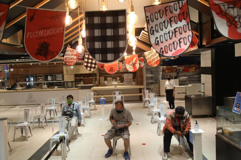 Food riders wait for orders at Siam Paragon in Bangkok, where, like other shopping malls, the only areas open are supermarkets and the food section for takeaway. (Photo: Arnun Chonmhatrakool)