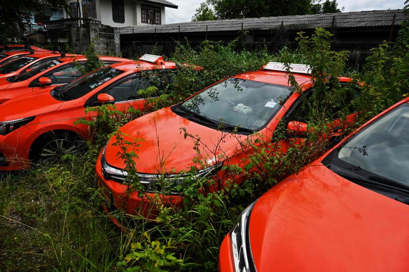 Weeds are seen growing around taxis parked at a company parking lot, after drivers were unable to pay rent on them due to the economic hardship of Covid-19 and more than a year of no incoming foreign tourism, in Bangkok, on July 20, 2021. (AFP file photo)