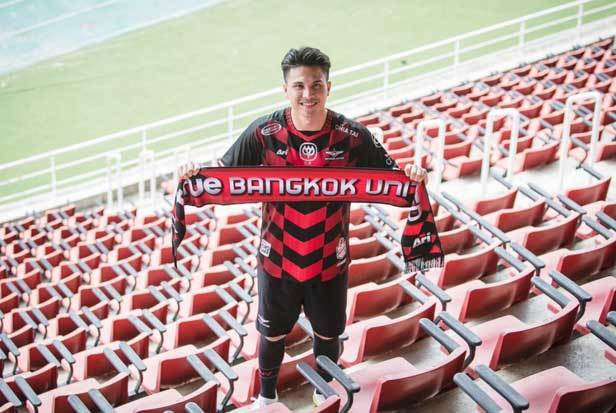 Thitiphan Puangchan poses with a Bangkok United scarf at True Stadium.