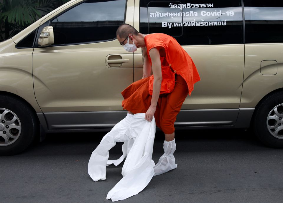 Buddhist monk Phrompong Kaino puts on personal protective equipment (PPE) to perform coronavirus disease testing in a community near his temple in Bangkok, Aug 4, 2021. (Reuters photo)