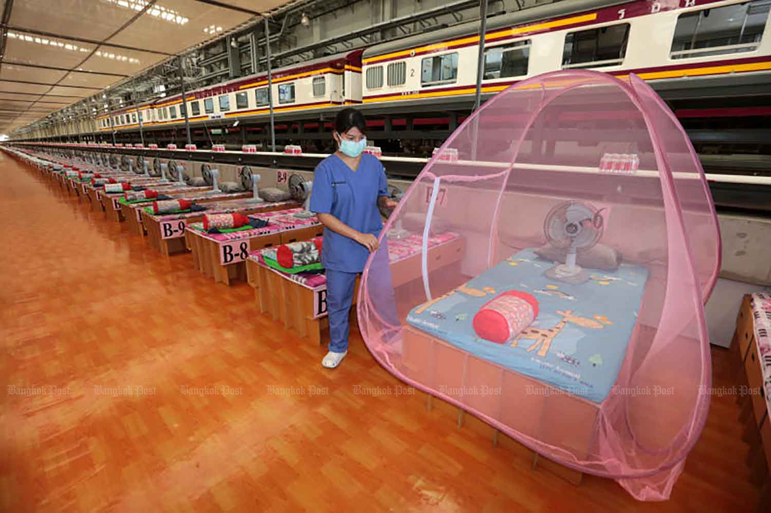 A worker shows how a mosquito net is put up over a bed inside a new community isolation centre at the train maintenance depot at Bang Sue Grand Station in Bangkok on Tuesday. The centre cares for Covid-19 sufferers with few or no symptoms. (Photo: Chanat Katanyu)