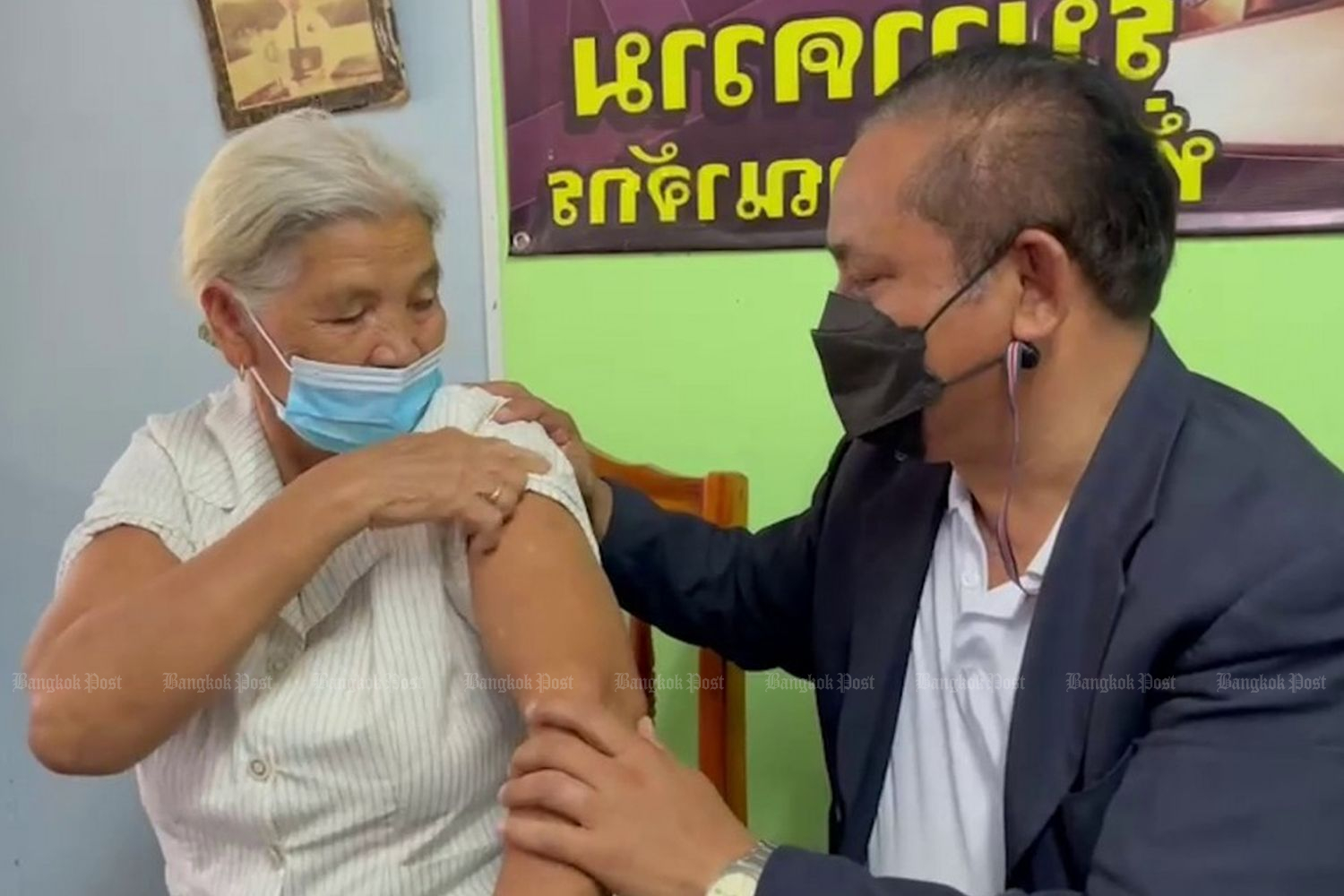 Somwang Jukul (left) shows an arm in a video with her son, while talking to Thai media about how she got two shots of the AstraZeneca vaccine on Saturday.