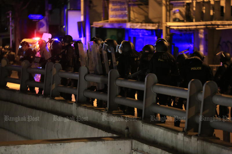 Police officers are stationed on a flyover during a clash with protesters in Din Daeng area on Monday. (Photo: Pornprom Satrabhaya)
