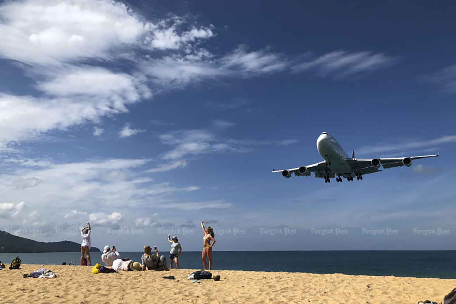 Tourists pose for pictures at Mai Khao beach in Phuket in 2019. Mai Khao beach is a popular destination for tourists looking to snap a few selfies with planes as they approach directly overhead, flying low before landing on the runway. (Bangkok Post file photo)