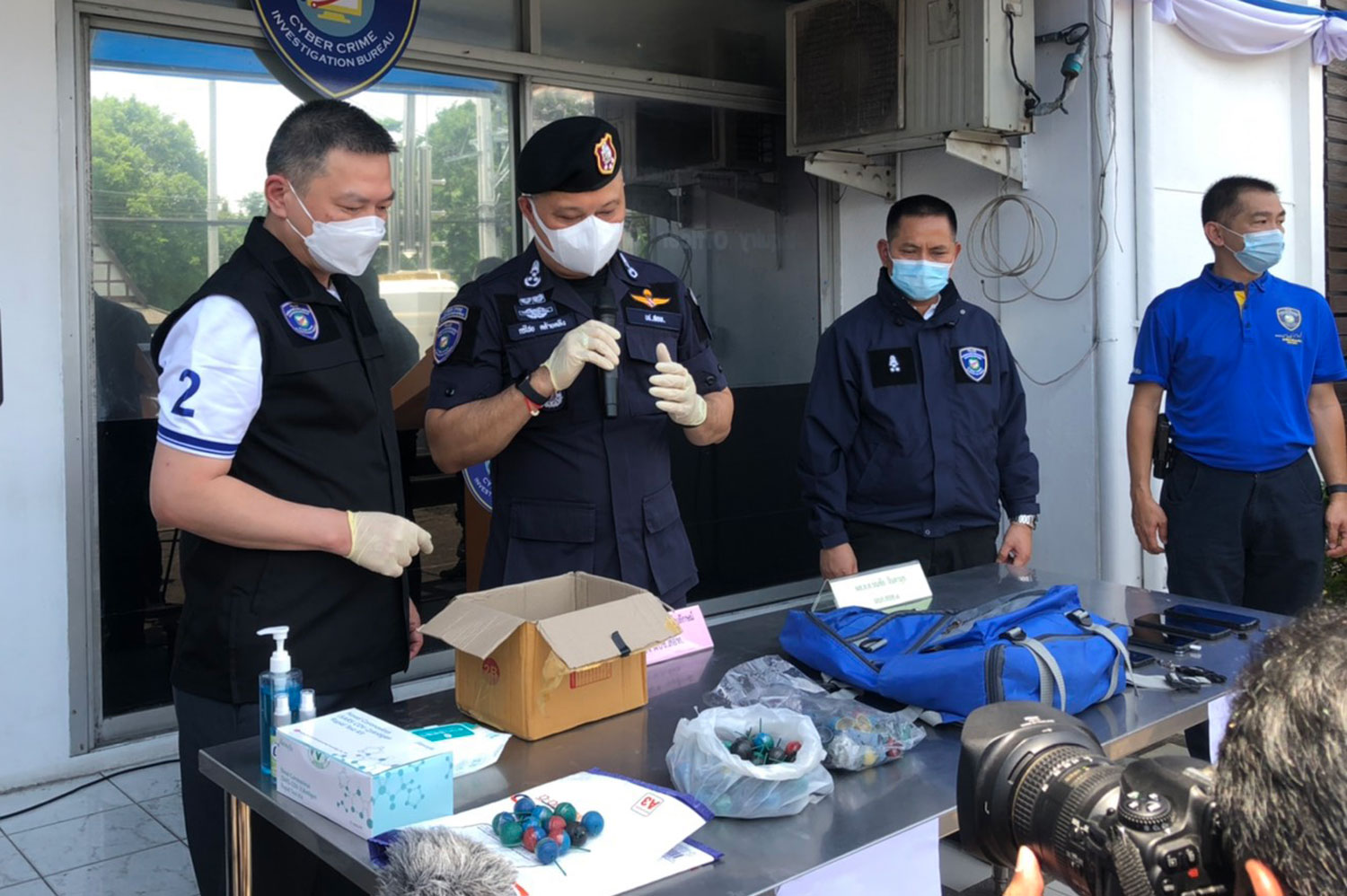 Pol Lt Gen Kornchai Klaiklueng (second from left), commissioner of the Cyber Crime Investigation Bureau, examines ping-pong bombs at a media briefing on Friday. (Photo supplied)