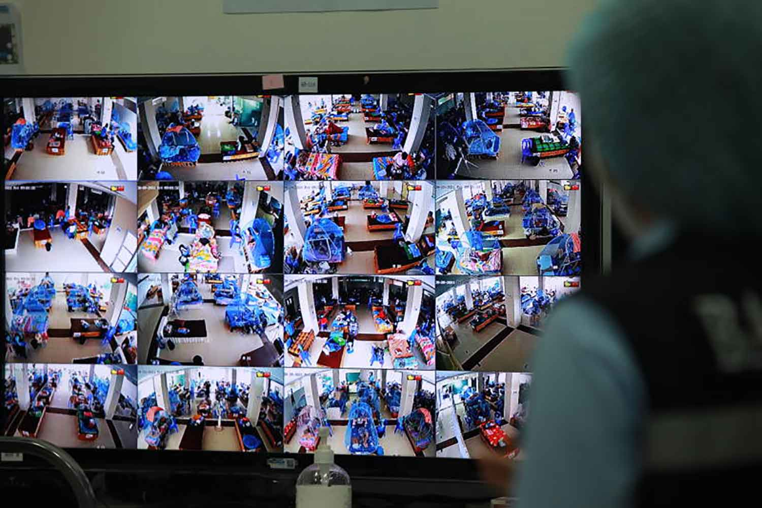 The monitor shows Covid-infected people on Friday rest at a flood response centre which the Bangkok Metropolitan Administration turned into an isolation facility in Prawet district. (Photo: Apichart Jinakul)