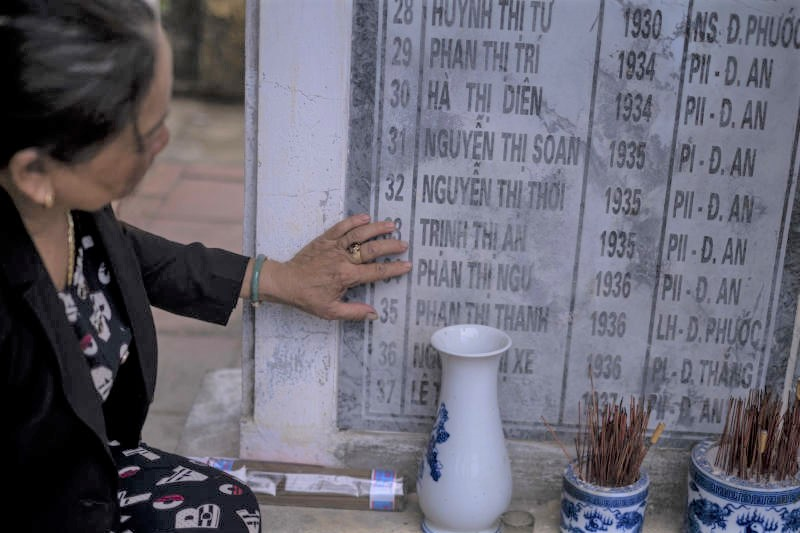 Nguyen Thi Thanh, a survivor of Phong Nhi and Phong Nhat massacre carried out by South Korean troops fighting alongside Americans, points out the names of relatives at a memorial in the Quang Nam Province of Vietnam, July 13, 2021. Victims are seeking compensation from the Seoul government in the first lawsuit of its kind being tried in a South Korean court. (Linh Pham/The New York Times)