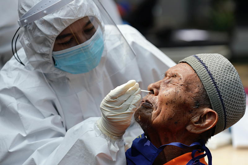 A healthcare worker wearing personal protective equipment (PPE) takes a swab sample from an elderly man with mental illness to test for the coronavirus disease (Covid-19) at a social home in Jakarta, Indonesia, on Monday. (Reuters photo)