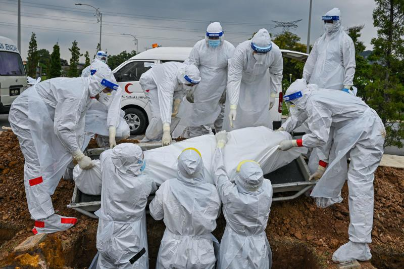 FILE PHOTO: Volunteers wearing protective suits lay down the body of a Covid-19 coronavirus victim for burial at the Raudhatul Sakinah Muslim cemetery in Kuala Lumpur on June 15, 2021. (AFP)