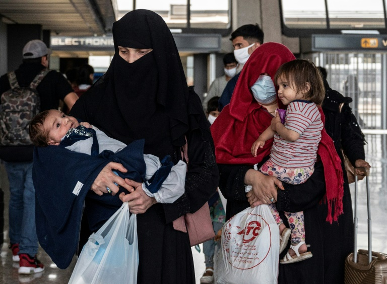 Refugees from Afghanistan are escorted to a waiting bus after arriving at Dulles International Airport in Dulles, Virginia.