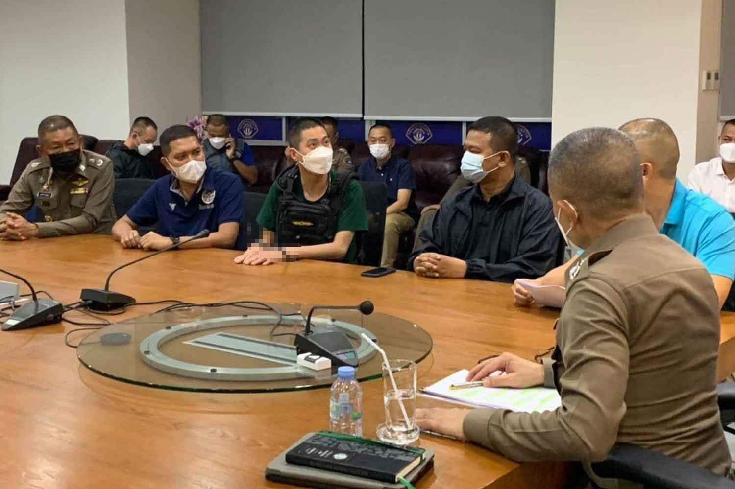 Pol Col Thitisan Utthanaphon (handcuffed) is at the Crime Suppression Division in Bangkok on Thursday night as national police chief Pol Gen Suwat Jangyodsuk (right) questions him. (Police photo)
