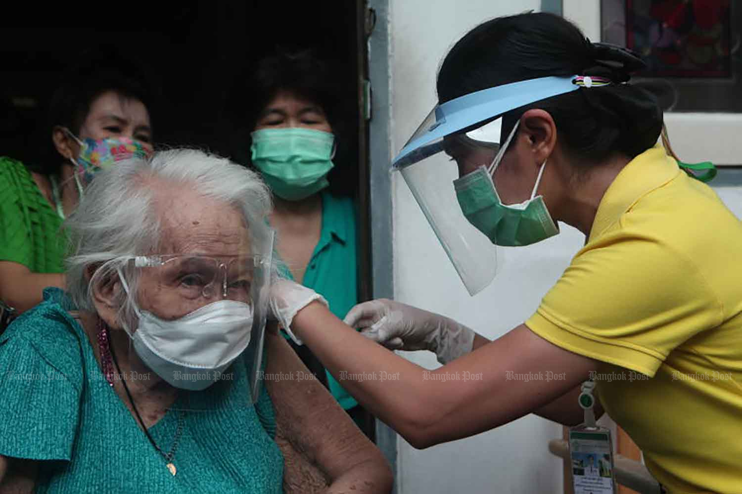 A health worker gives the AstraZeneca vaccine to a bedridden patient, Malai Phensut, 96, at her home in Sathon district, Bangkok, on Thursday. (Photo: Apichart Jinakul)