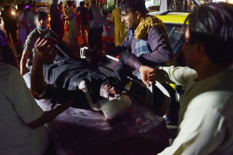 Medical and hospital staff bring an injured man on a stretcher for treatment after two blasts, which killed at least five and wounded a dozen, outside the airport in Kabul.