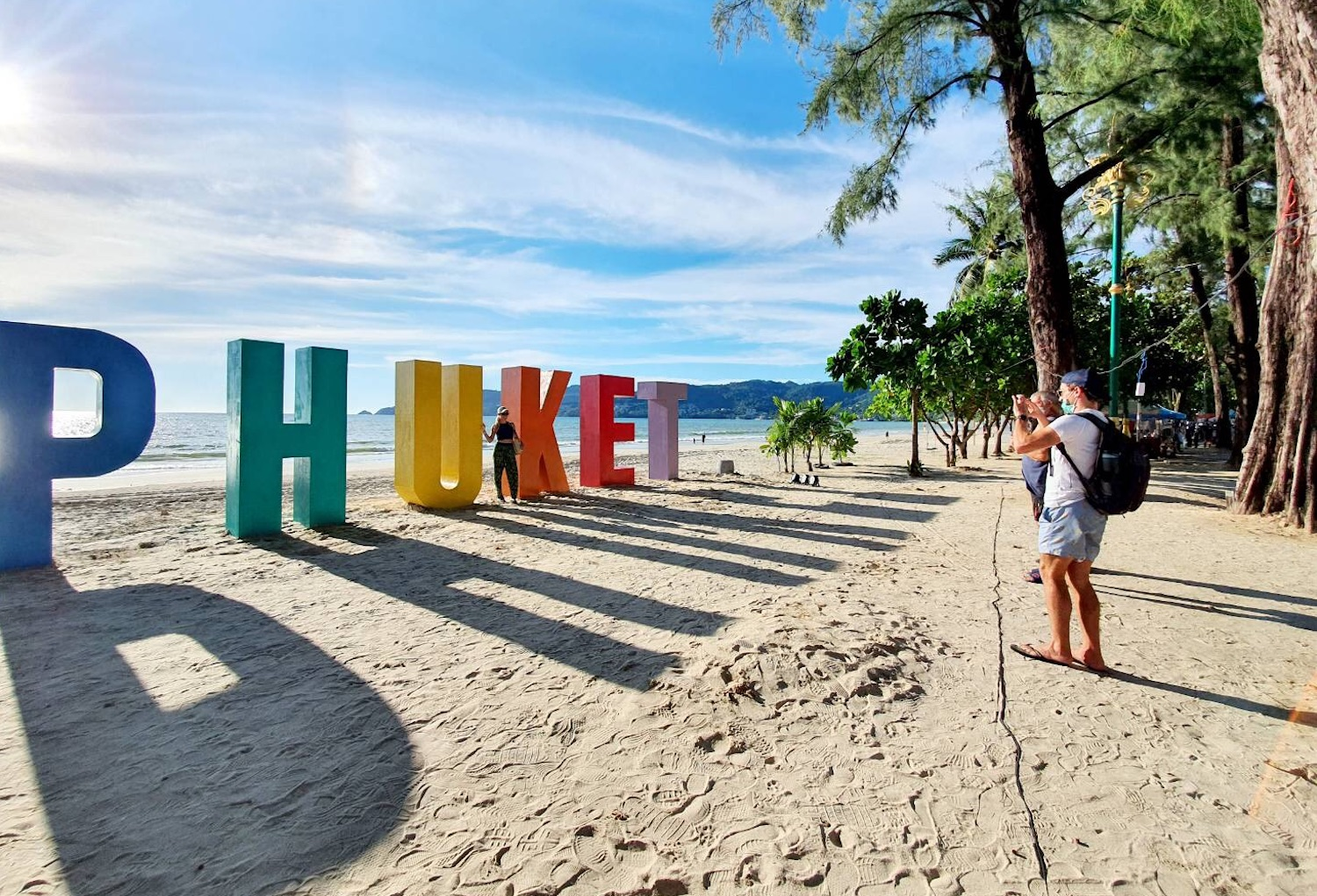 A tourist takes a picture on a beach in Phuket, which has been open to fully vaccinated international visitors since the start of July.