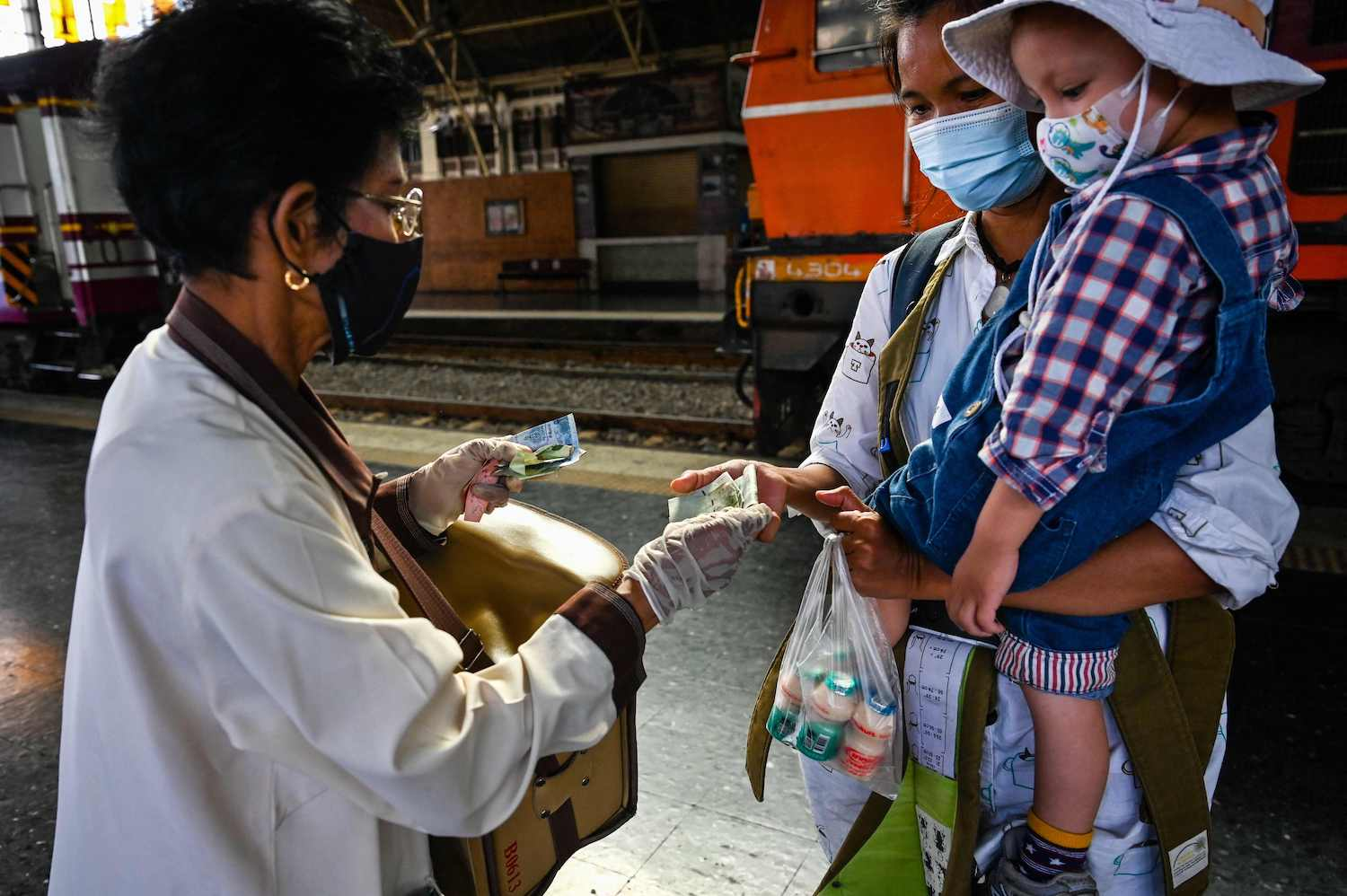 A woman buys drinking yoghurt from a vendor at Hua Lamphong station. (AFP Photo)