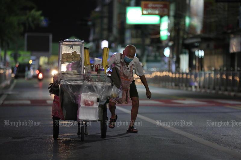 A street-food vendor struggles to push his cart along an almost deserted road near Nonthaburi's main pier at night on July 24, 2021. (Photo: Pornprom Satrabhaya)