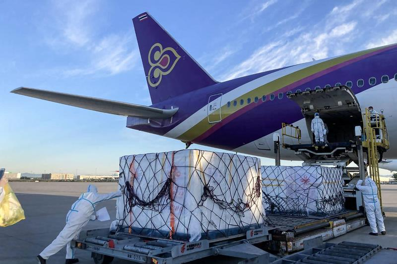 In this handout photo taken on June 5, 2021 and released on June 9 by Thai Airways, airport personnel handle the shipment of 500,000 doses of Sinovac vaccines for the Covid-19 coronavirus from China on arrival at Suvarnabhumi International Airport in Bangkok. (AFP PHOTO / THAI AIRWAYS)