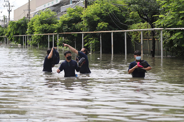 Workers wade through floodwater on Sunday after Saturday night downpours submerged the Bangpoo Industrial Estate in Muang district of Samut Prakan. (Photo: Sutthiwit Chaiyutworakan)
