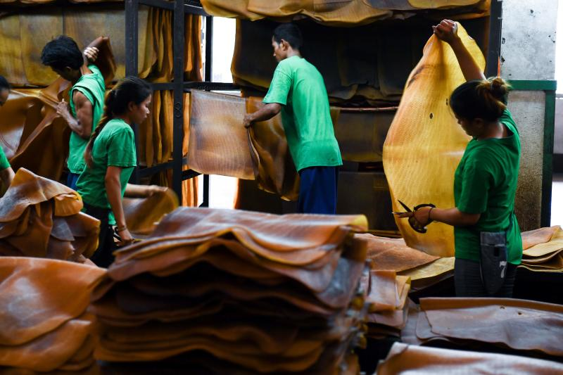 FILE PHOTO: Workers sort out raw rubber sheets at a factory in Rayong province on Oct 17, 2018. (AFP)