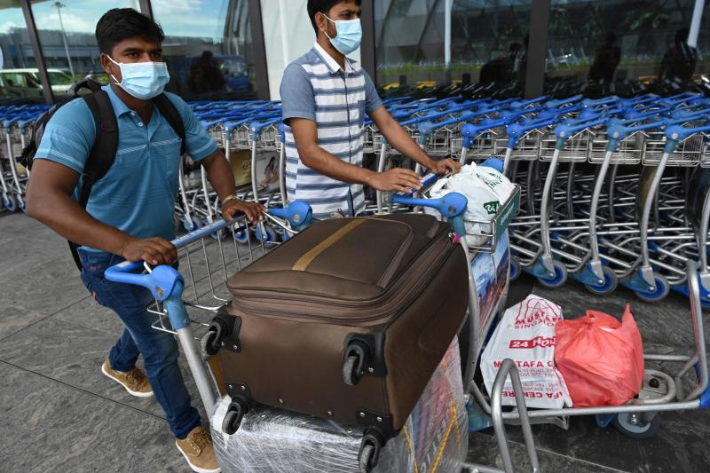 A migrant worker departing for home pushes his luggage on a trolley outside the departure hall at Changi International Airport in Singapore on Aug 19, 2021. (AFP photo)