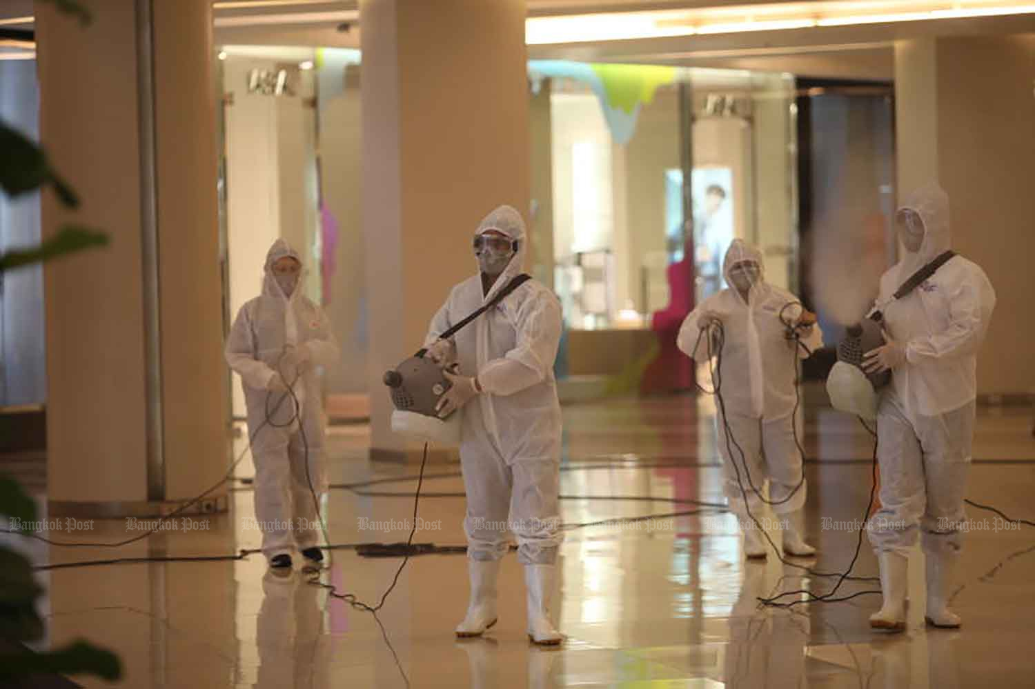 Workers spray disinfectant at a shopping centre in Bangkok on Monday to prepare for reopening on Wednesday. (Photo: Apichart Jinakul)
