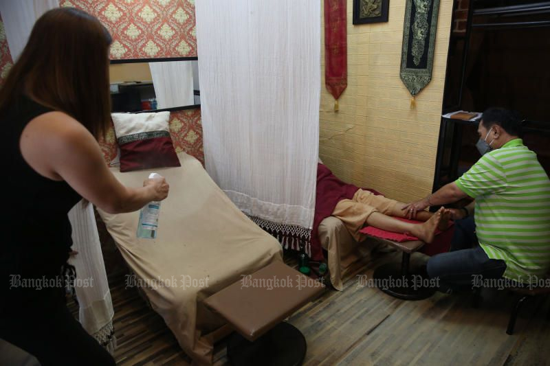 A masseuse sprays disinfectant on a reclining chair while her colleague massages a customer on the first reopening day at a foot massage shop in Bang Kapi district of Bangkok on Wednesday. (Photo: Varuth Hirunyatheb)