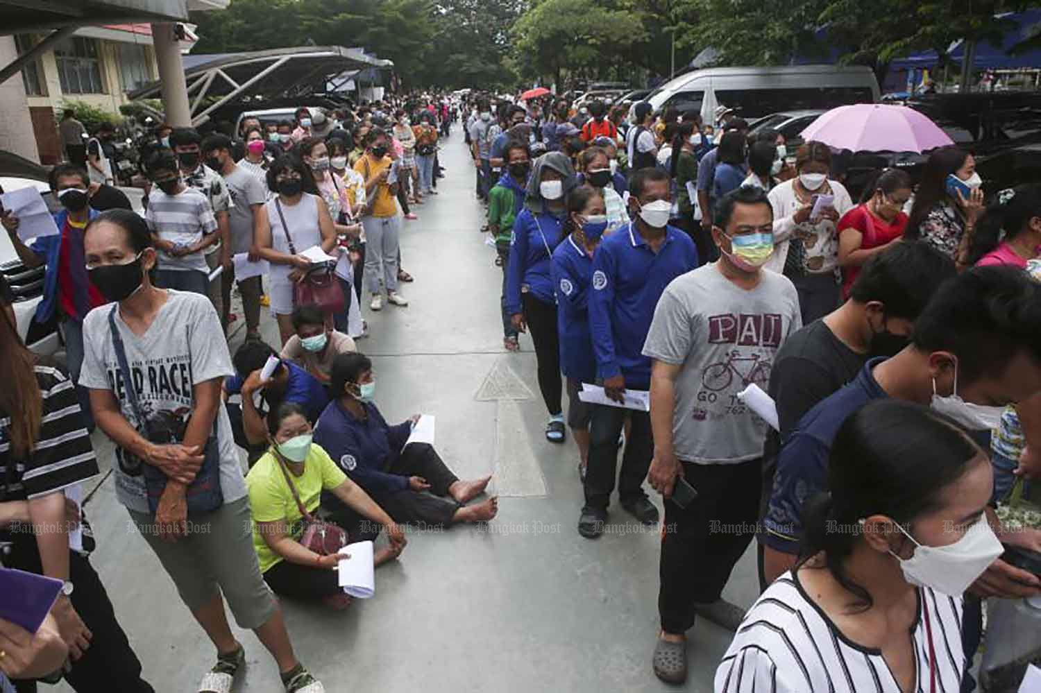 People wait to receive a Covid-19 vaccine in the parking lot at the Nonthaburi  municipal office. The municipality is offering 500 Sinopharm jabs each day on a walk-in basis to individuals aged 18 and over who have yet to register for vaccination, until the supply runs out. (Photo: Pattarapong Chatpattarasill)