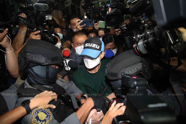 Pol Col Thitisan Utthanaphon, centre, is taken into custody at the Crime Suppression Division in Bangkok on Aug 26. (Photo: Arnun Chonmahatrakool)