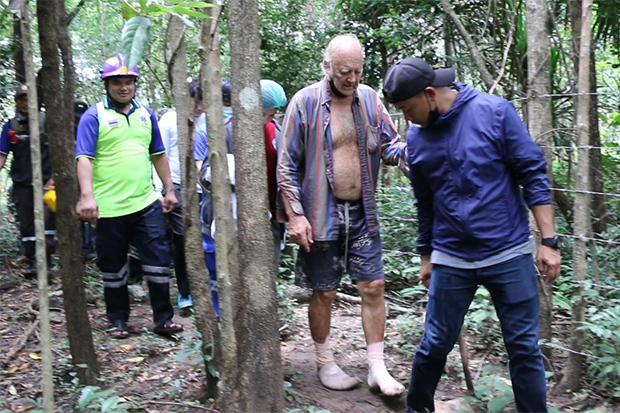 Rescuers accompany Barry Weller after finding him in the forest in Khao Suan Kwang district of Khon Kaen on Friday. (Photo by Chakkrapan Natanri)