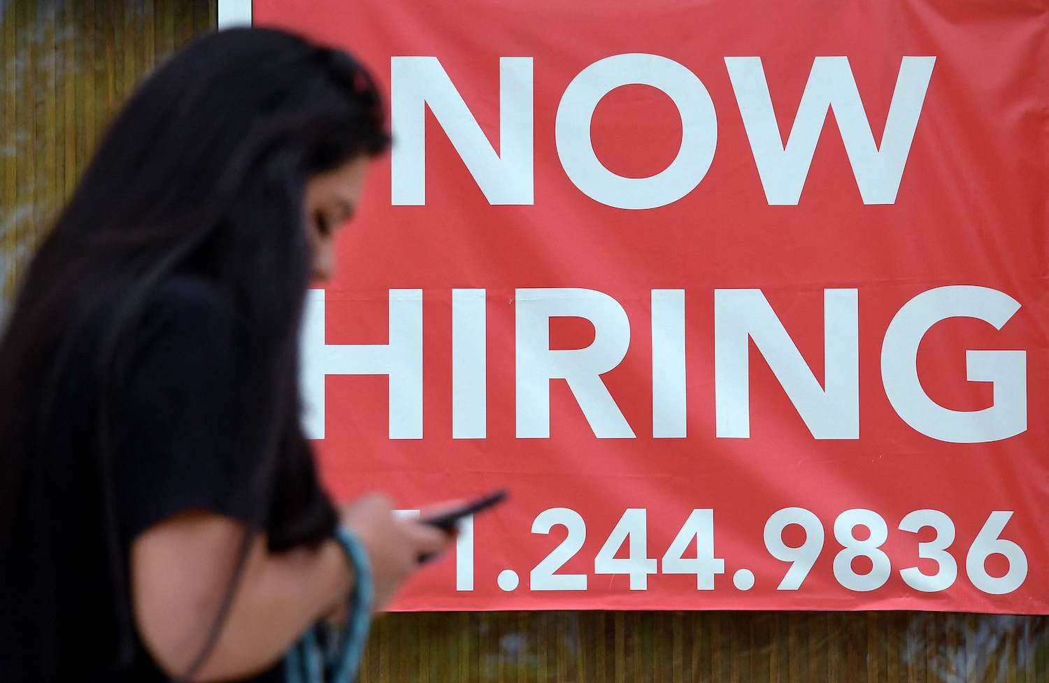 """A woman walks by a """"Now Hiring"""" sign outside a store in Arlington, Virginia in August. (AFP Photo)"""
