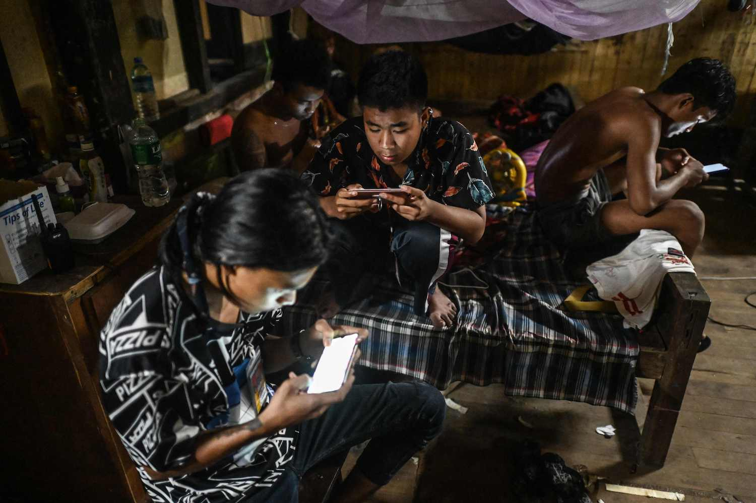 Volunteers play games on their smartphones at a temporary base where they are working to treat and bury Covid-19 victims in Taungoo district of Bago region, 220km northeast of Yangon. (AFP Photo)