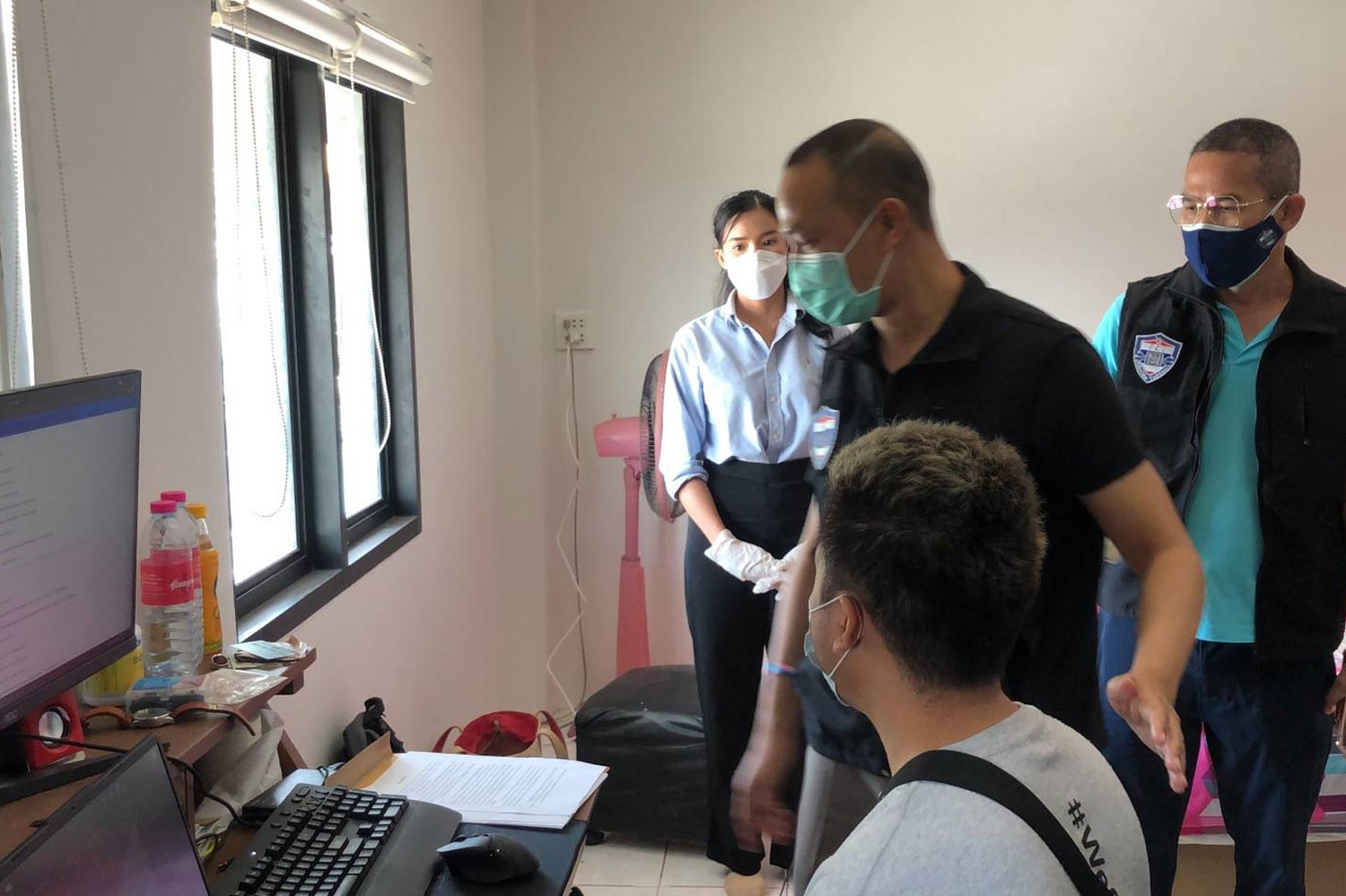 Police talk to one of six suspects arrested for allegedly running a gambling website during raids on three houses in Chon Buri on Saturday. (Photo supplied)