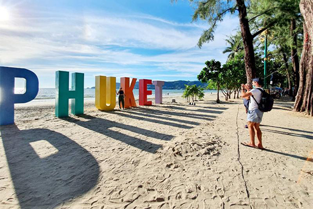 A tourist takes a photo with the colourful letters spelling the name of the island displayed on a beach in Phuket. (Tourism Authority of Thailand photo)