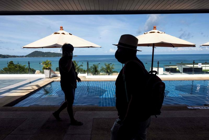 Guests walk past a hotel swimming pool in Phuket on Aug 14, 2021 as tourists take advantage of the