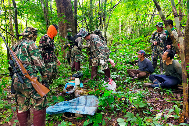 Two of three hunters sit on the ground after they were arrested by park rangers in Thong Pha Phum district of Kanchanaburi on Sunday. (Photo: Piyarat Chongcharoen)