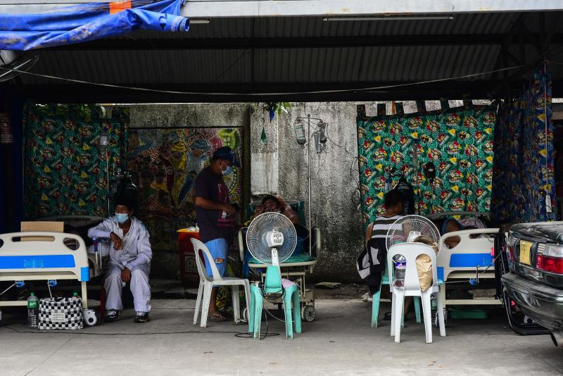 Relatives of suspected Covid-19 patients sit by their bedside while waiting in a car park turned into a Covid ward outside a hospital in Binan town, Laguna province south of Manila on Monday, with record infections fuelled by the hyper-contagious Delta variant. (AFP photo)
