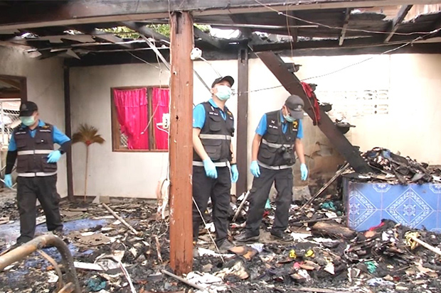 Forensic police examine the house destroyed by a fire started by drug addict Vararit Atkhampha in Chonnabot district of Khon Kaen on Monday morning. (Photo: Chakkrapan Natanri)