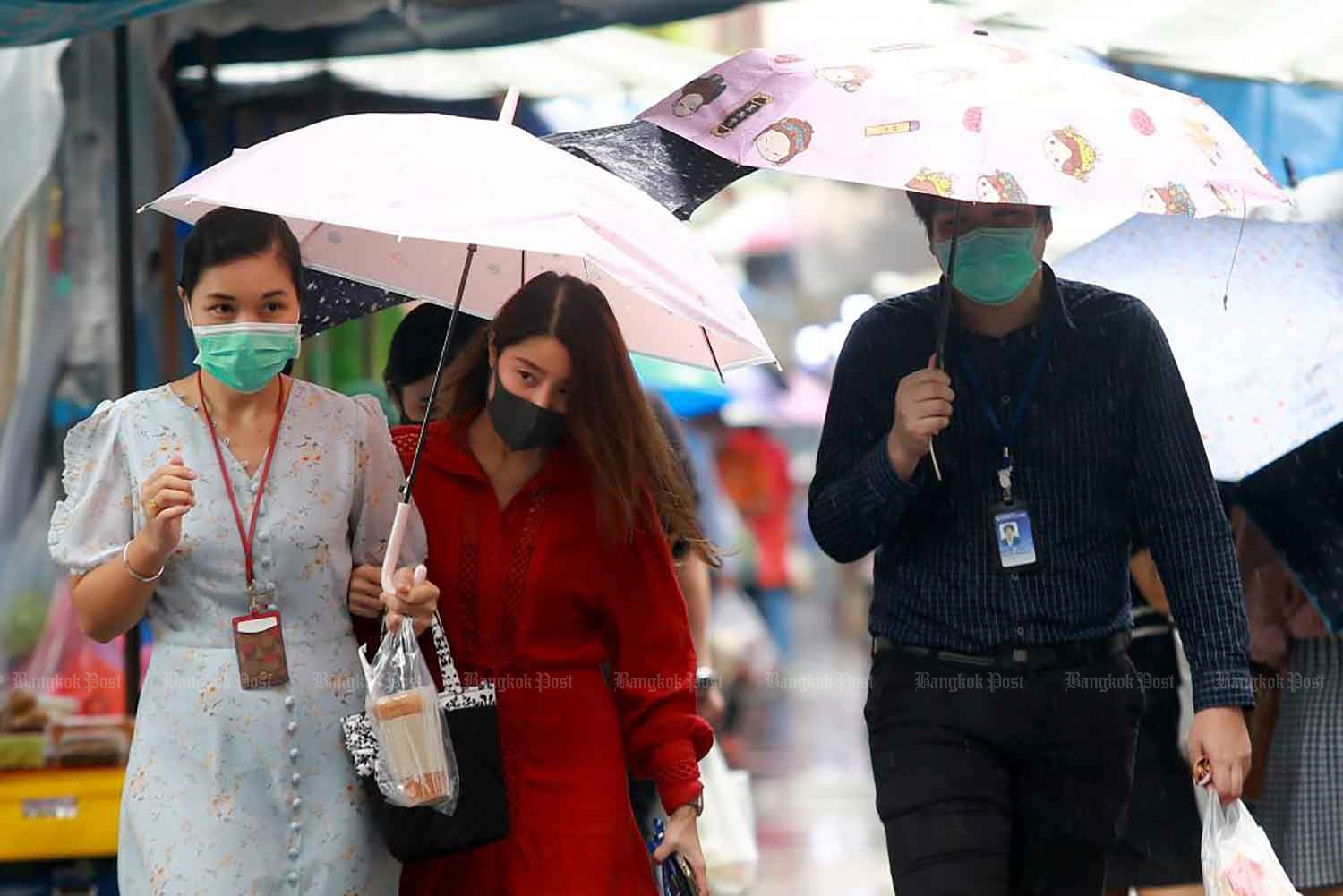Office workers use umbrellas as they walk on Silom Road in Bangkok on Tuesday during their lunch hour. More wet weather is forecast.(Photo: Somchai Poomlard)
