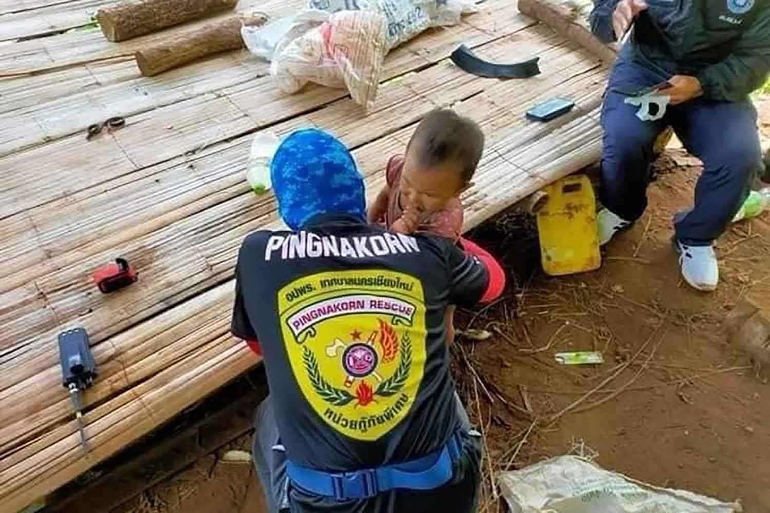 Rescue workers comfort Nong Gina at the hut where she was found, about two kilometres from her home in Mae Taeng district, Chiang Mai, around noon on Wednesday. (Photo: Panumet Tanraksa)